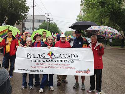 Des participants à la marche gaie dont Francine Proulx-Kenzle (1ère à gauche de la banderole) et Ken Bos (2e à droite de la banderole), personnes contact de PFLAG-Regina