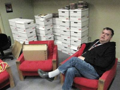 Le directeur de CFRG, Guylain Bergeron, montre avec fierté les boîtes contenant les 7 000 disques qu'il a reçus de Radio-Canada Edmonton.