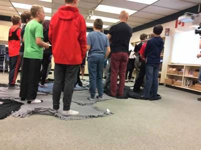 Vingt-huit  élèves de l'École St. Dominic Savio ont participé, le 12 octobre, à un «blanket exercise». Ils sont debout sur «Turtle Island».